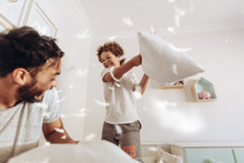 Boy Playing With His Father At Home With Pillows