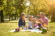 canvas print picture - Happy man and woman with smiles playing with children on the street and picnic