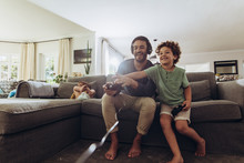 Father And Son Having Fun At Home Playing Video Game