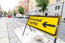 London, UK Road Closed Roadblock Diverted Traffic Yellow Sign Text In City Closeup With Street And Cars Traffic In Pimlico