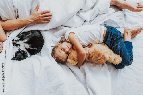 Fotografie, Obraz  Little girl sleeping with teddy bear in parents bed