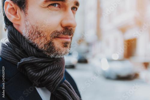plakat Calm man in black coat is walking in city