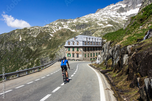 A cyclist descending on the way from Furka Pass (2.429 m), one of the most spectacular road in the Swiss Alps, Valais, Switzerland