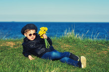 Portrait Of A Boy With Daffodils . Boy In Nature Holding A Bouquet Of Spring Flowers