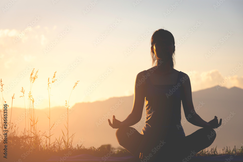 Fototapeta silhouette fitness girl practicing yoga on mountain