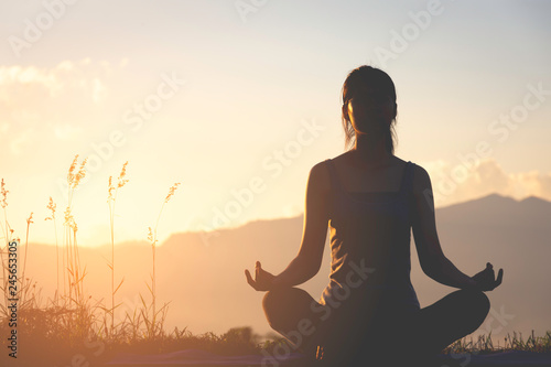 Poster Relaxation silhouette fitness girl practicing yoga on mountain