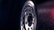 Side view of abstract car wheel driving back on black road. Close up for car wheel with silver disc moving back on abstract black asphalt road.