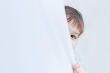 Funny Boy Three Years Old Looks Out From Behind The Curtains, Plays Hide And Seek