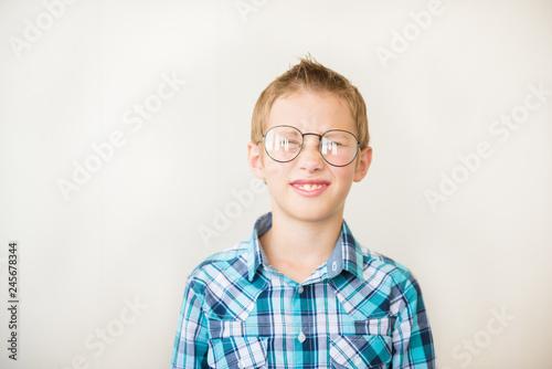 Fotografía  Teenager kid boy squints in myopia correction glasses