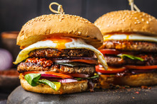 Homemade Meat Burgers With Egg, Sauce And Vegetables On Dark Background.
