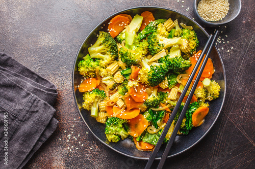 Photo  Vegan wok stir fry with broccoli and carrot in black dish, top view, copy space