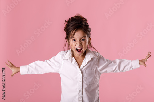 Fotografering angry little child girl in white shirt with hairstyle