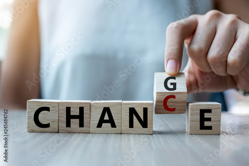 Foto Businesswoman hand holding wooden cube with flip over block CHANGE to CHANCE word on table background
