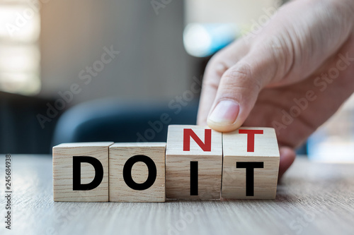 Fotomural  Business man hand holding wooden cube with flip over block DON T to DO IT word on table background
