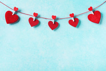 Valentines Day Background. Garland Of Red Hearts On Clothespins On Turquoise Wall.