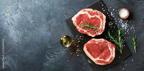 Obraz Fresh meat on slate black board top view. Raw beef steak and spices for cooking. - fototapety do salonu