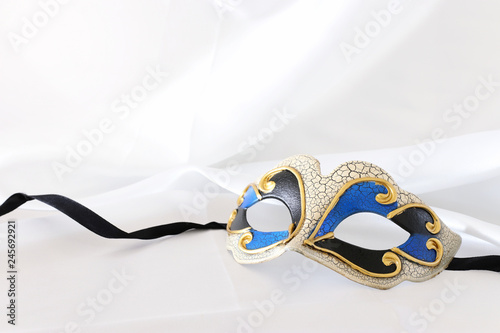 Photo of elegant and delicate venetian mask over white silk background.