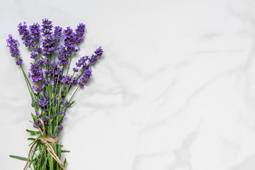 Beautiful lavender flowers bouquet on white marble table with copy space for your text. top view. flat lay