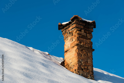 Cuadros en Lienzo Crumbling old brick chimney on old abandoned house at wintertime.