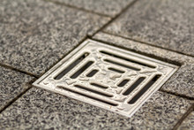 Water Drain Vent In Kitchen, Bathroom Or Basement Ceramic Tiled Old Vintage Floor. Geometric Abstract Beige Background.
