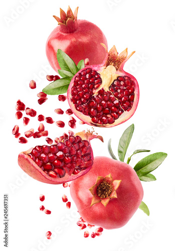 Fotografie, Obraz Flying in air fresh ripe whole and cut pomegranate with seeds and leaves