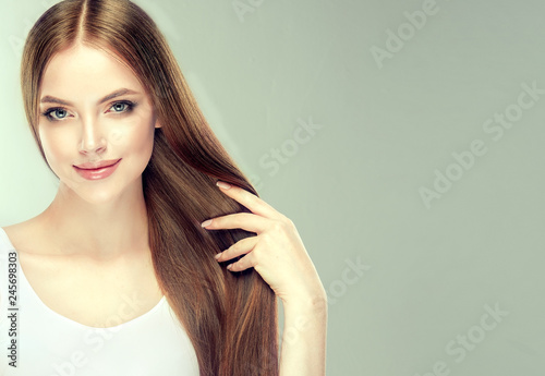 Beautiful model girl with shiny brown and straight long  hair . Keratin  straightening . Treatment, care and spa procedures. Smooth hairstyle