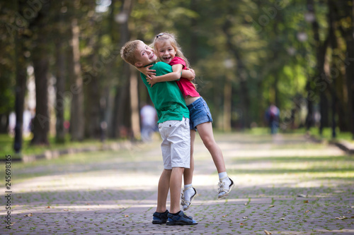 Fototapeta Two cute young funny smiling children, girl and boy, brother holding sister in his arms, having fun on blurred bright sunny park alley green trees bokeh background. Loving siblings relations concept. obraz