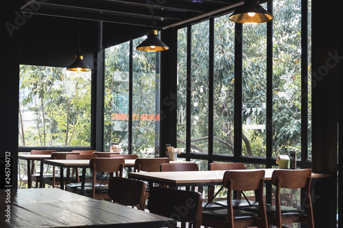 Table and chair set in modern cafe minimalistic interior design with big window Fototapete