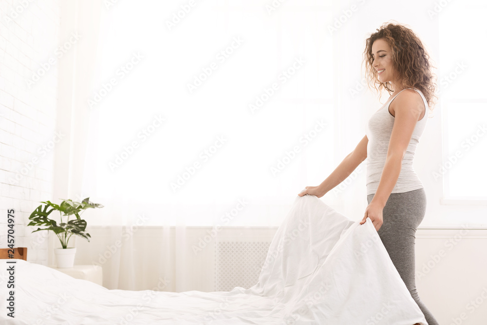 Fototapeta Young woman making bed and organizing room