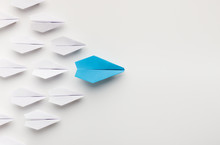 One Blue Paper Plane Leading Group Of White Ones