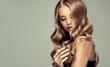 Leinwandbild Motiv  blonde girl with long  and   shiny wavy hair .  Beautiful  smiling woman model with curly hairstyle .