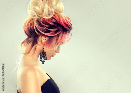 Beautiful model girl  with elegant  multi colored hairstyle . Stylish Woman with fashion  hair  color highlighting.   Creative  red and pink roots ,   trendy  coloring.