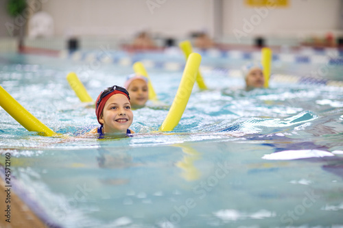 Happy little girl in swimming cap learning to swim with swim noodle at the lesson in pool