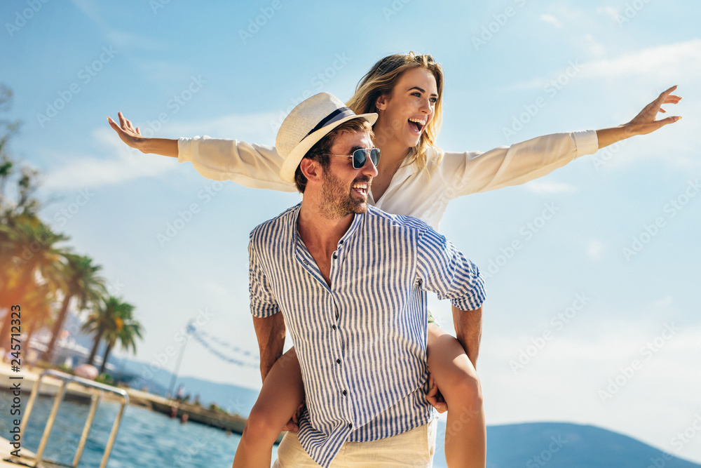 Fototapety, obrazy: Couple in love, enjoying the summer time by the sea.Joyful girl piggybacking on young boyfriend having fun.
