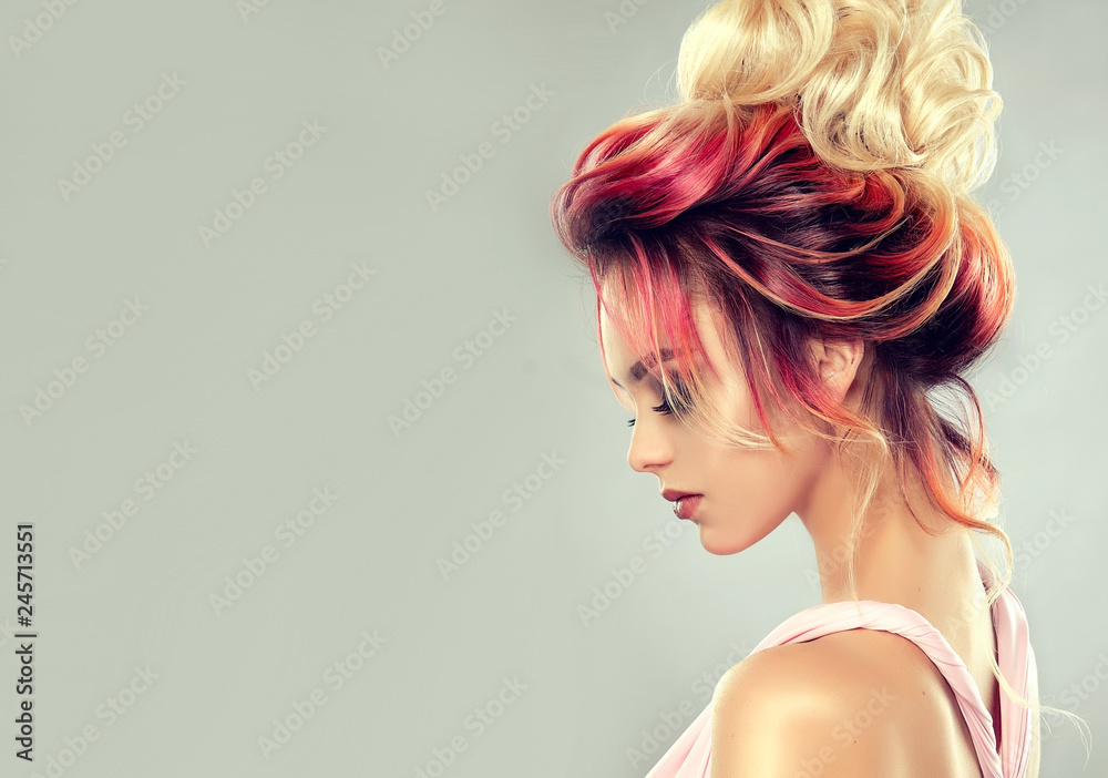Fototapeta Beautiful model girl  with elegant  multi colored hairstyle . Stylish Woman with fashion  hair  color highlighting.   Creative  red and pink roots ,   trendy  coloring.