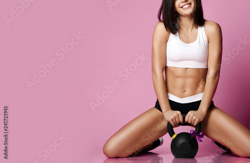 Fitness Girl working out with big weight dumbbell happy smiling on pink Canvas-taulu