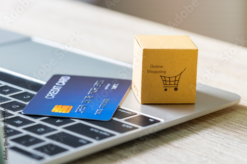 Cardboard box with text online shopping and mock up of credit card on laptop keyboard Wallpaper Mural