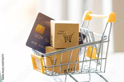 Fotografía  Stack of cardboard boxes with text online shopping and mock up of credit card in trolley
