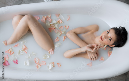 Canvas-taulu Sensual brunette business lady taking homemade skin care spa procedure in bathroom, enjoying with milky aromatic bath and rare moments of peace and quiet