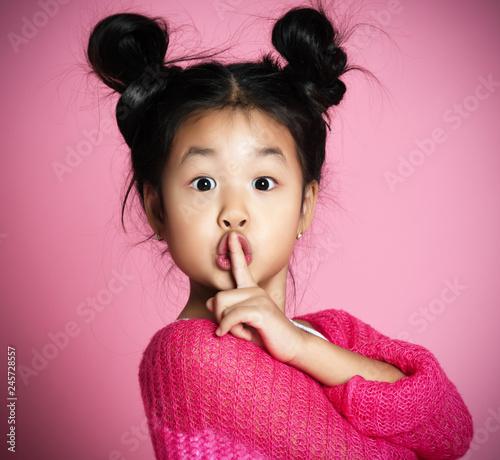 Fotografie, Obraz  Asian kid girl in pink sweater shows shh sign Close up portrait