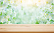 Natural background with blooming jasmine flowers and wooden table. Empty table on blurred floral background