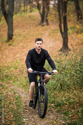 Aluminium Prints Cycling Young man in black t-shirt on sports bike against the background of the autumn city park, concept of healthy lifestyle, copy space.