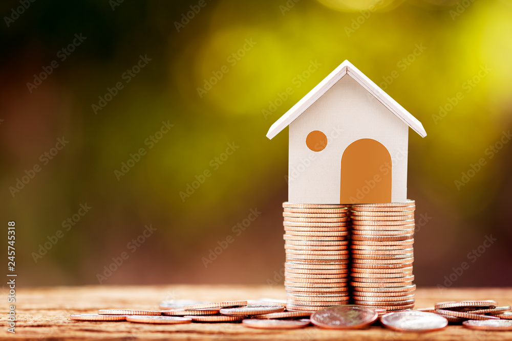 Fototapeta Loan or saving money for buy a house and real estate for family concept, Home model put on the stack coin tower with growing business investment in the in the public park.