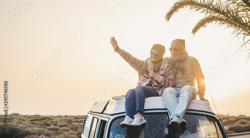canvas print motiv - simona : Travel and enjoying life lifestyle in love for couple in relationship sitting on the roof of a old vintage romantic van with sunset and sunlight golden tones background - forever together wanderlust