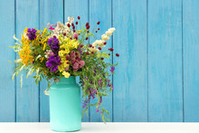 Bouquet Of Wild Flowers In Starm Tin Can Vase On Background Blue Wooden Boards. Template For Postcard Copy Space Lettering Text Or Design Concept Women's Day, Mothers Day, Hello Summer Or Hello Spring
