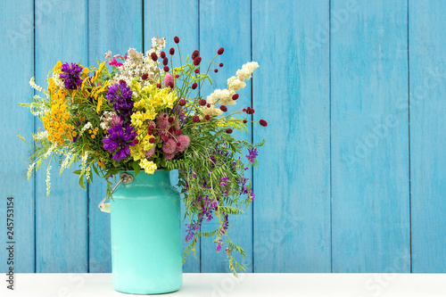 Papiers peints Fleur Bouquet of wild flowers in starm tin can vase on background blue wooden boards. Template for postcard Copy space lettering text or design Concept Women's day, Mothers Day, Hello summer or Hello spring