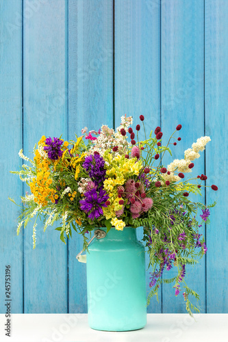 Bouquet of wild flowers in starm tin can vase on background blue wooden boards Wallpaper Mural