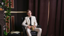 Bored Teen Student Guy In White Business Suit Sitting In A Chair With A Book By The Fireplace