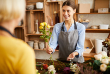 Waist Up Portrait Of Smiling Young Woman Selling Flowers To Client While Working In Flower Shop, Copy Space