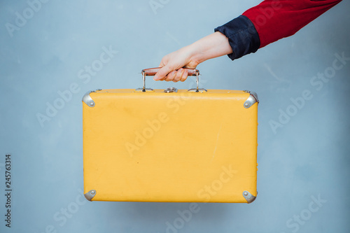 Carta da parati The hand of a girl in a red jacket holds a vintage yellow suitcase on a blue bac